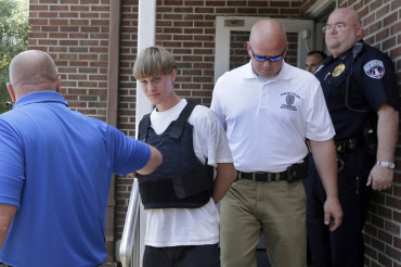 The most hated man in America smirks as he is hauled away in handcuffs, bullet-proof vest