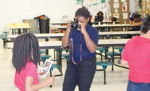 Ma'liya James, a fourth-grader and a member of the schools Manatee Messenger staff documents the distribution of the first edition of the school's paper.