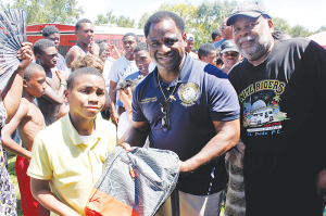 Kashief Williams, 10, is handed the first backpack at the family bash by State Rep. Wengay Newton and Nite Riders president Donnie Williams.